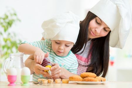 Mother and little girl making cookies together at kitchen