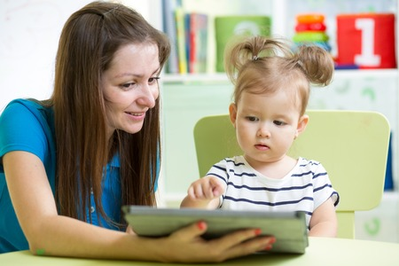 mother and kid daughter with tablet pc photo