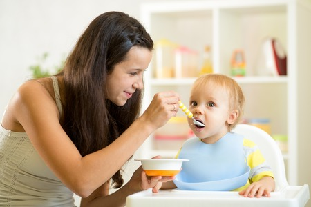 a little dinner: Mother spoon-feeding her child boy at kitchen