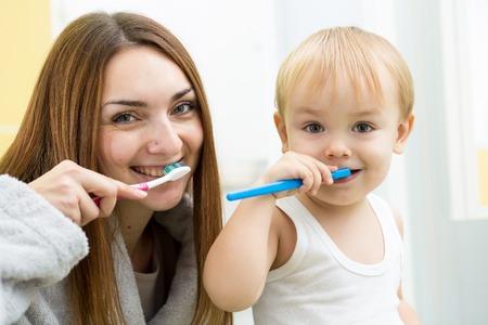 mom and child boy brushing teeth in bathroom photo