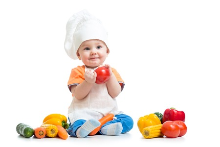 Baby die een chef hoed met fesh groenten Stockfoto
