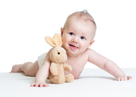 funny baby boy lying with plush toy Stock Photo