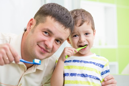 father and kid son brushing teeth in bathroom photo