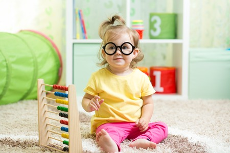 child with eyeglasses playing abacus at home