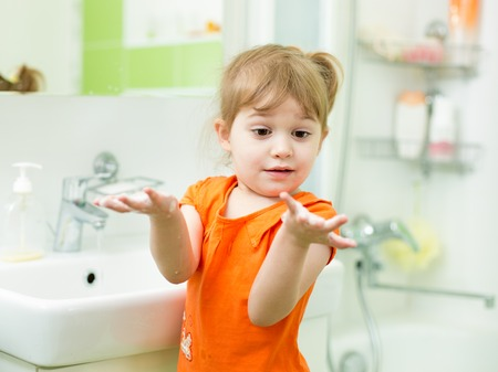 Funny kid girl washing hands in bathroom photo