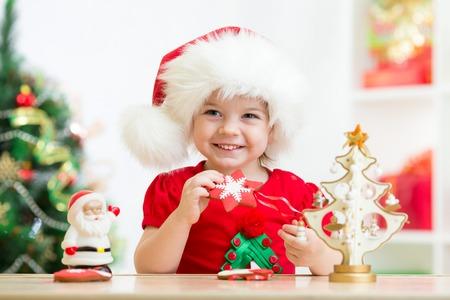 kid girl in Santa hat holding Christmas cookies photo