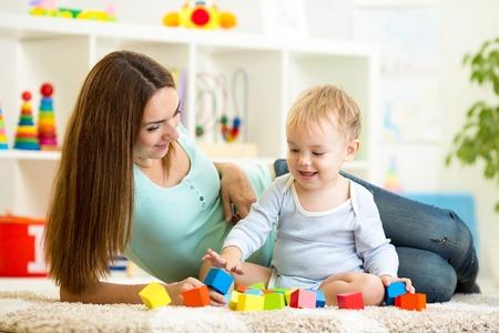 schattige moeder en haar zoon samen indoor spelen Stockfoto