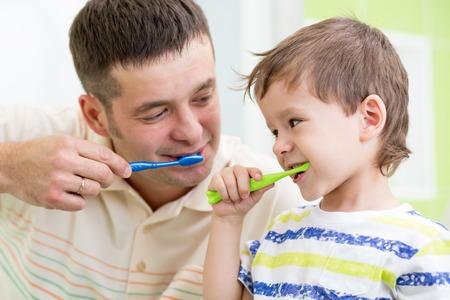 father and kid son brushing teeth in bathroom photo