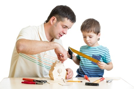 Father and son kid making wooden nesting box together