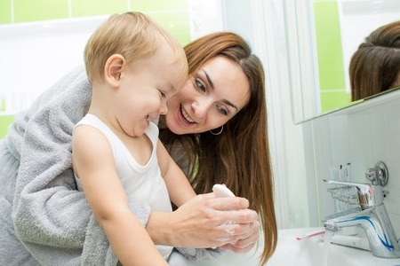 Happy mother and kid wash hands with soap in bathroom photo