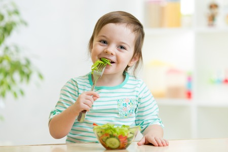 eating: kid girl eating healthy vegetables at kitchen Stock Photo