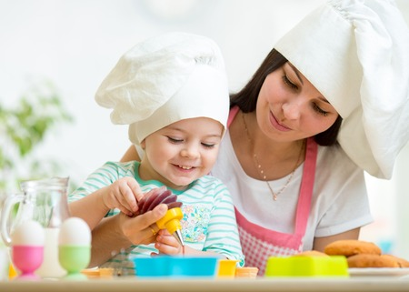 Mother and kid girl making cookies together
