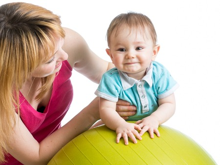 fit ball: mother playing with baby boy on fit ball
