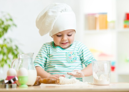 smiling baker kid girl in chef hat at kitchen photo
