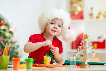kid girl in Santa hat making christmas tree of plasticine photo