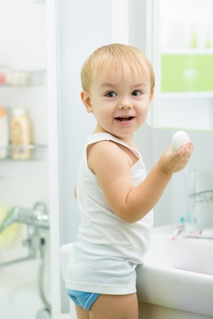 child toddler boy washing hands with soap in bathroom photo