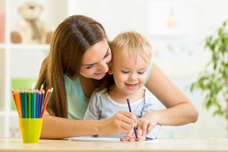 child boy and mother drawing with colorful pencils photo