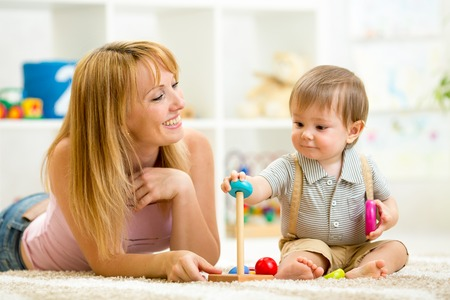 babysitter: cute woman and kid play together indoor