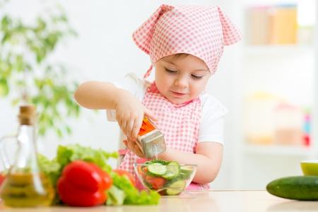 cute kid girl preparing vegetables at kitchen