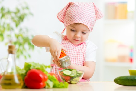 cute kid girl preparing vegetables at kitchen