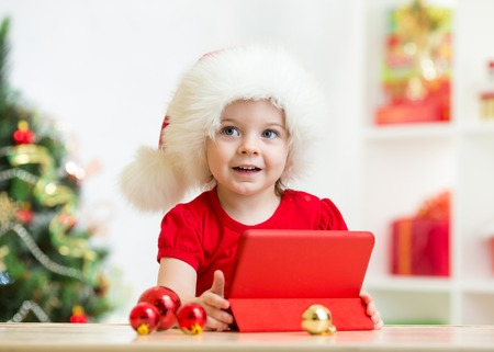 Happy kid girl in christmas hat with tablet pc photo