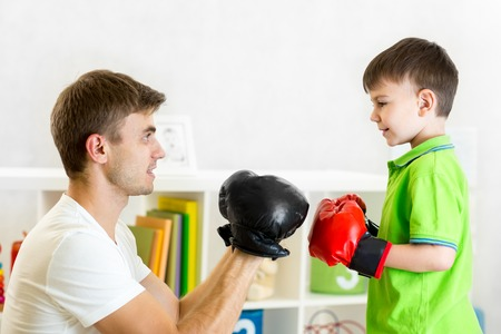 boxing boy: kid boy and father play with boxing gloves Stock Photo