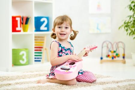 instrumentos musicales: cabrito juega el juguete de la guitarra en casa Foto de archivo