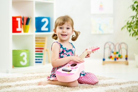 instruments de musique: enfant fille jouer de la guitare jouet � la maison