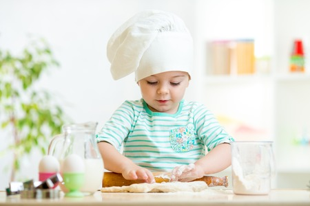 little baker kid girl in chef hat at kitchen Stock Photo