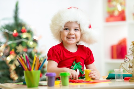 child girl making christmas tree of plasticine photo