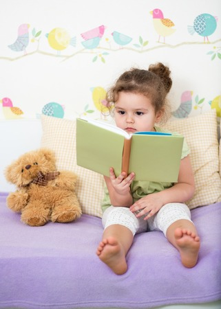 child girl reading book for teddy bear Imagens