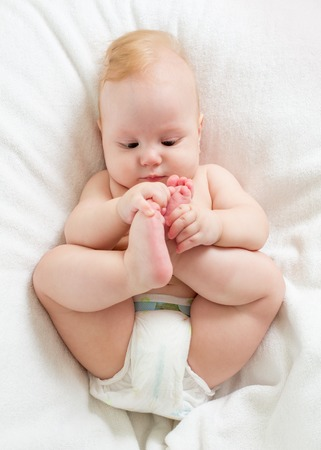 baby boy lying on white sheet and holding his legs Stock Photo