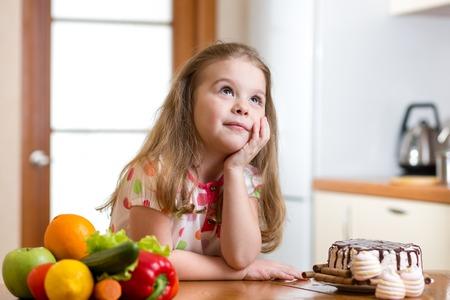 kid girl choosing between healthy vegetables and tasty sweets photo