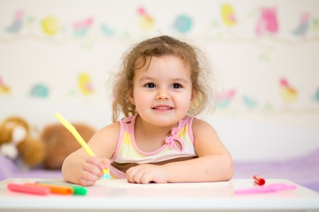education concept: kid girl paints in her nursery at home