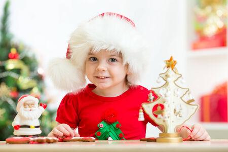 santa cap: kid girl in Santa hat holding xmas cookies Stock Photo
