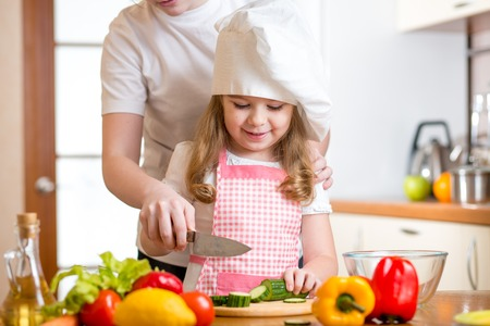 mother and kid girl cooking and cutting vegetables on kitchen photo