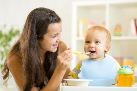 baby eating: Beautiful young woman feeds son baby at home
