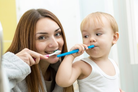 mother and her kid son brushing teeth in bathroom photo