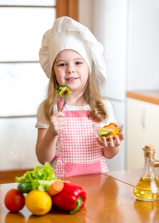 child girl in cook hat eating food vegetables photo