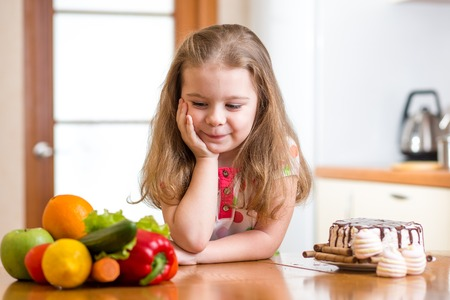 child girl choosing between healthy vegetables and tasty sweets photo