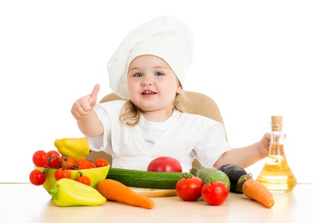 beautiful little girl with food vegetables over white photo