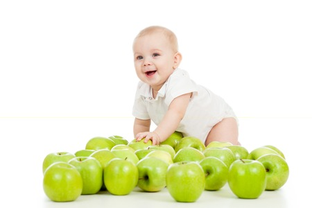Smiling baby boy with many green apples photo