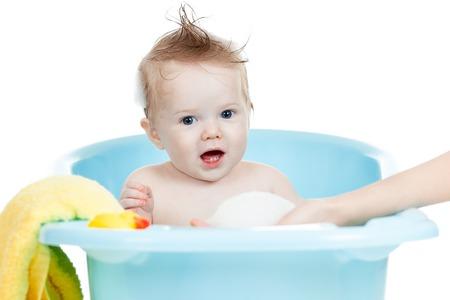 adorable baby boy taking bath in blue tub photo