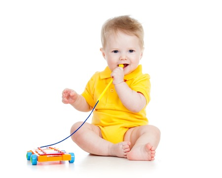 baby boy playing  with musical toy isolated photo