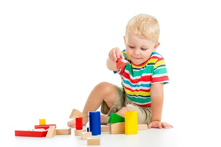 kid boy playing  wooden toy blocks isolated photo
