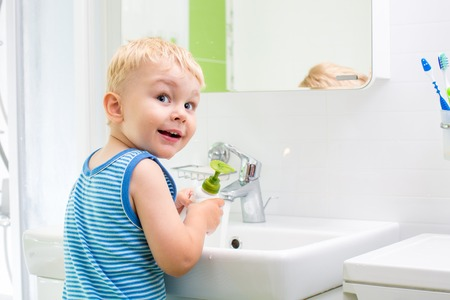 soap sud: kid boy washing his face and hands with soap in bathroom