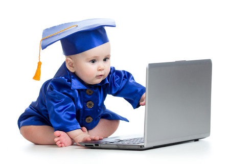 academic dress: baby in academic dress works on laptop isolated