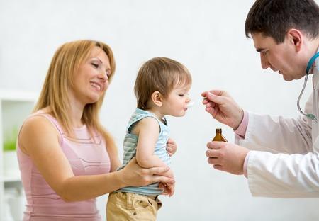 pediatra: Pediatra dando dosis cucharada de jarabe de beber l�quido medicina a pacientes beb� Foto de archivo
