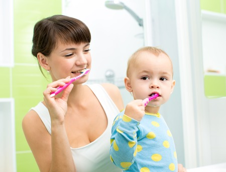 smiling mother and kid daughter brushing teeth in bathroom photo