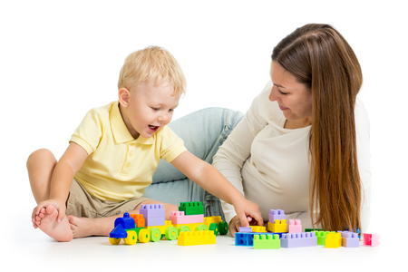 kid boy and mother playing together with construction set toy photo